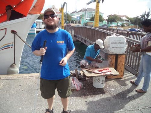 Next to the boat, a man selling fish on a small wooden board.