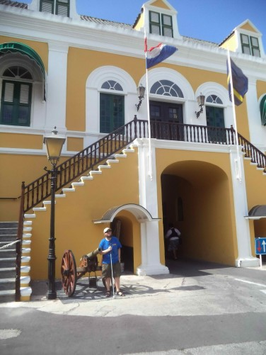 Tony at Fort Amsterdam by a canon. The Dutch and Curaçao flags flying above an entrance. The fort was constructed in 1634 by the Dutch West India Company and served not only as a military fort but also as the headquarters of the Dutch West India Company.