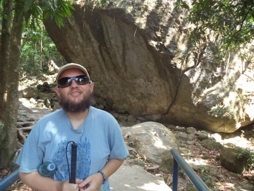 Tony standing in the jungle on a small bridge near Chorro Macho (Macho Waterfall). A large boulder behind.