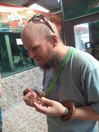 Tony now handling a smaller reddish-brown coloured snake.