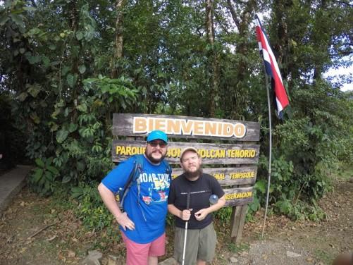 Tony and Mario by a welcome ('Bienvenido') board at Tenorio National Park.