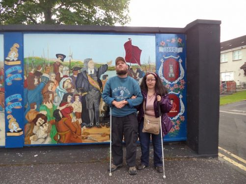 Tony and Tatiana in front of a mural located in the unionist Fountain estate. It depicts a scene from the 1688–1691 war between supporters of Catholic King James II and those of the Dutch Protestant Prince William of Orange.