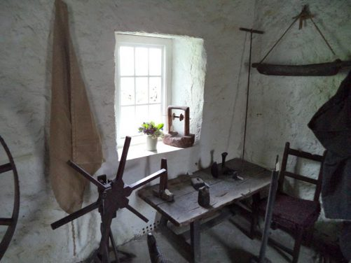 Inside the same dwelling, a wooden table and chair with various domestic wooden and metal implements.