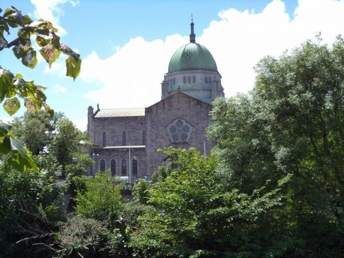 View over trees to the Cathedral of Our Lady Assumed into Heaven and St Nicholas. The cathedral was built on the site of the old city prison and was consecrated in 1965. It has an eclectic style including a central Renaissance Revival dome.