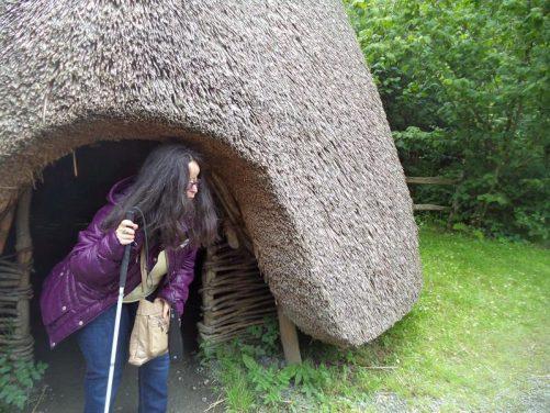 Tatiana emerging from a replica prehistoric hut.