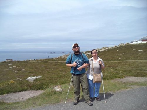 Tony and Tatiana at Land's End with a good view out to sea. The rocky Longships islets can be seen in the distance with Longships Lighthouse standing amongst them. The Longships are situated roughly 1.25 miles (2 km) west of Land's End.