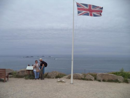 Tony and Tatiana with the Atlantic Ocean and the Longships rocks in the background. A flag pole flying the Union Jack along side.