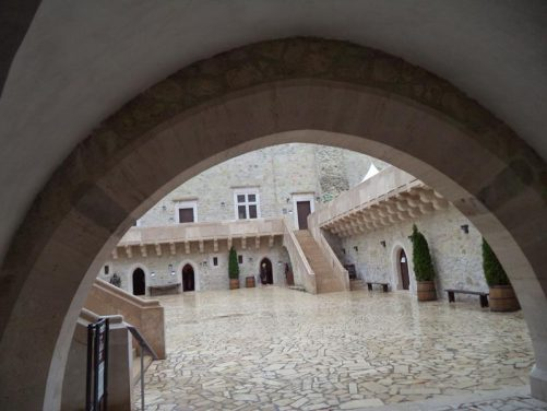 Looking into the lower courtyard through a stone archway. Behind is a long building that contains the public toilets, gift shop and lift to the second floor.