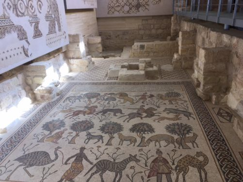 An impressive floor mosaic depicting people hunting wild animals, such as a lion, zebra and wild boar.