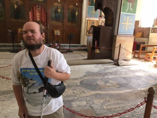 Tony in front of the Madaba Map, a 6th century mosaic map of the Holy Land, located inside the 19th-century Greek Orthodox St George Church.