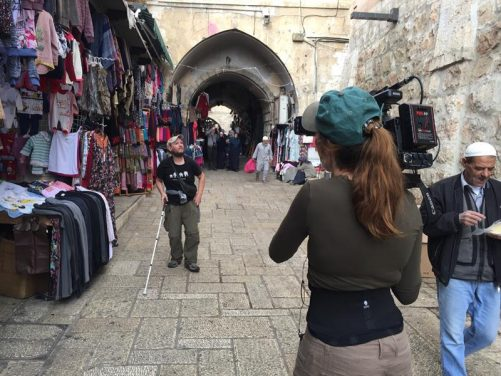Almudena filming Tony in the markets of the Old Town, Jerusalem. In view are stalls selling clothes and a stone archway behind.