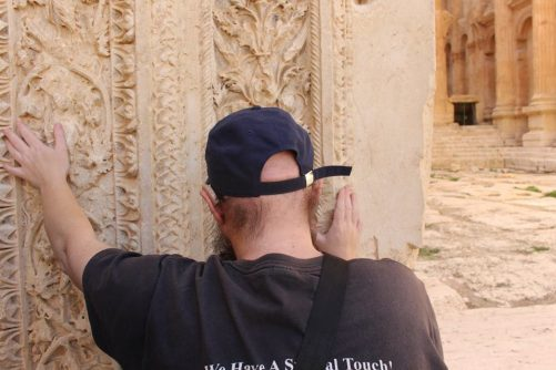 Tony touching an intricately carved stone block at the entrance to the Temple of Bacchus.