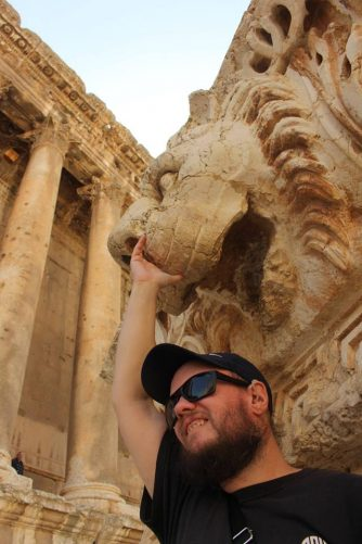 Tony standing smiling underneath a lion statue. Right arm touching just underneath the lion's nose.