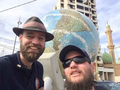 Thor and Tony in front of a large globe, a public artwork in Sidon.