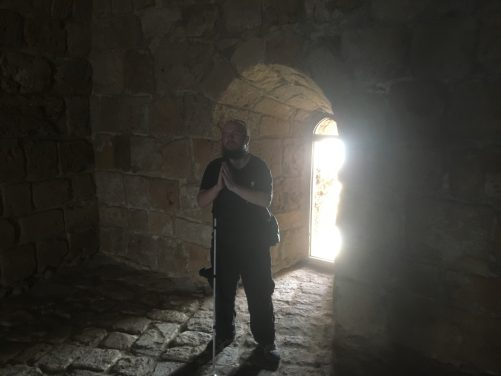 Tony pretending to pray at Sidon Sea Castle. He is standing in the doorway of a dimly lit room.