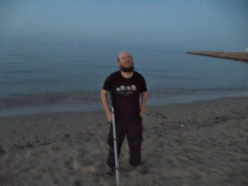 Tony standing on a small sandy beach in Sur. Evening.