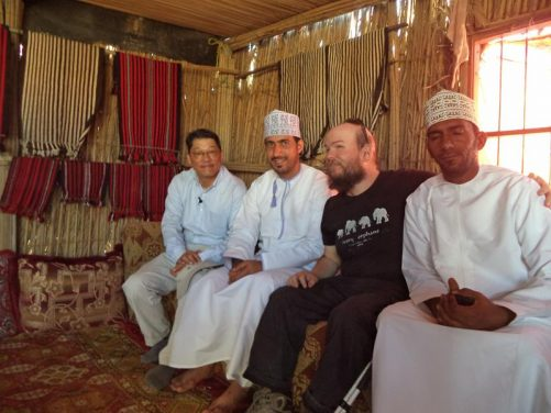 Tony sitting with three men inside a Bedouin camp at Wahiba Sands. It is the main building of the family (sleeping quarters seem to be elsewhere). It is traditionally built from wood and plant material. Two of the men are Omani Beduin, wearing traditional white robes and embroidered caps. The third guy is from South Korea.