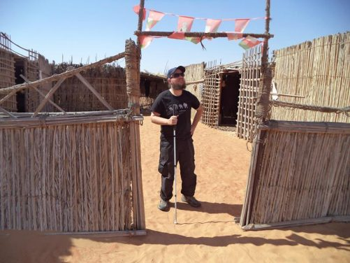 Tony in a courtyard/enclosure outside the main Beduin building. Again walls all made of wood and other plant material. Sand under foot.