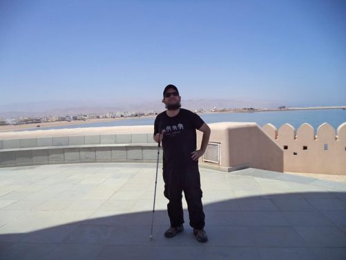 Tony standing in the shade of the lighthouse tower. In the distance, the buildings of Sur extending along the coast.