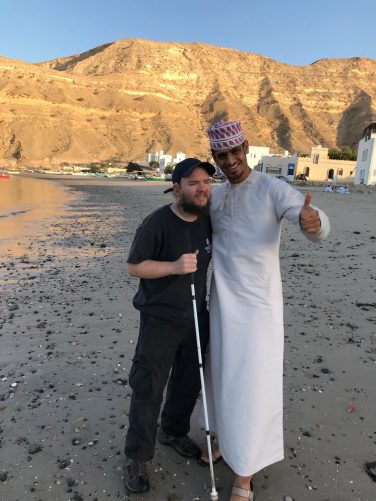 Tony and Ahmed on quiet, sandy Qantab Beach, a village and beach area north of central Muscat. Mainly known by locals. Small buildings on the edge of the beach behind. Barren sandy looking hill raising up in the middle distance.