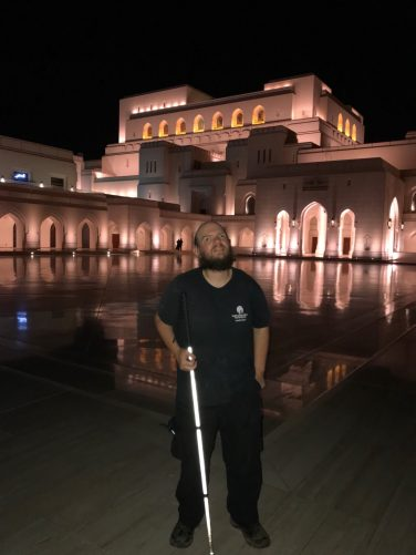 Tony outside Muscat Royal Opera House in the evening. This large white palatial-looking building opened in 2011.
