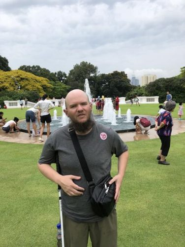 Tony in front of a formal pond with fountains in the Istana grounds.