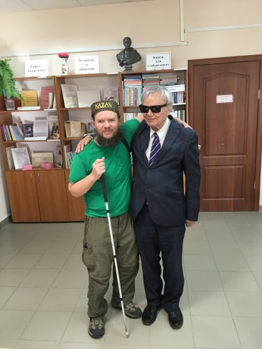 Tony and an older man standing together for the photo. The man is smartly dressed in a suit and wearing dark sunglasses. He is the director of the Library for the Blind and Visually Impaired. He is also blind.