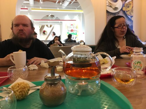 Tony and Tatiana sitting in a local café. A glass pot of tea is in the foreground. A candle is underneath to keep it warm. Tea seems to be more widely drunk than coffee in this part of Russia.