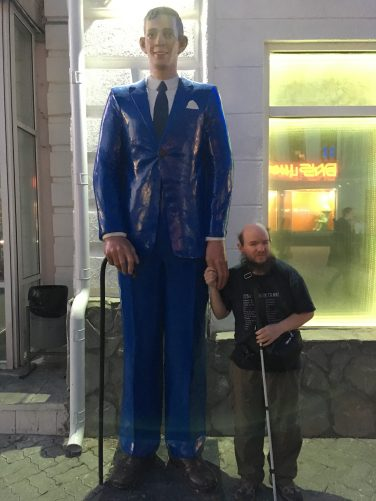 Tony standing by a statue of a very tall man in Bauman Street (Kazansky Arbat). The metal statue is more than twice Tony's height. The man is dressed in a blue suit and holding a walking stick.