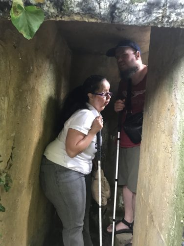 Tatiana and Tony in a short concrete passageway. This is one of the many trenches on the site. View from the entrance with a short flight of concrete steps lead up to a machine gun emplacement at the end, but they are mostly out of view.