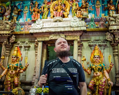 Tony inside the Sri Veeramakaliamman temple standing in front of an altar. The altar includes many idols, all brightly painted. One of Singapore's oldest Hindu temples, the Sri Veeramakaliamman Temple, dedicated to the goddess and destroyer of evil, Sri Veeramakaliamman or Kali.