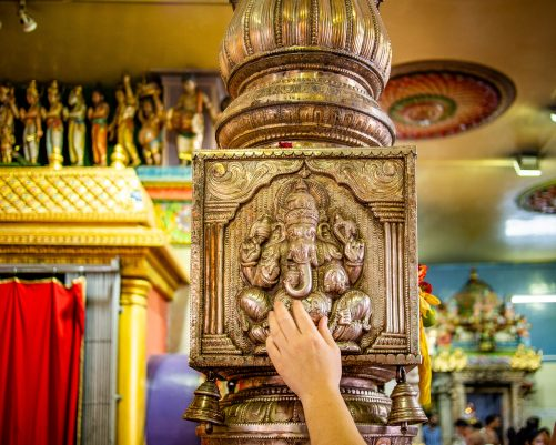 Tony touching an elaborately embossed metal pillar featuring the elephant God Ganesha. Inside Sri Veeramakaliamman temple. The Hindu deities Ganesha, is widely revered as the remover of obstacles.
