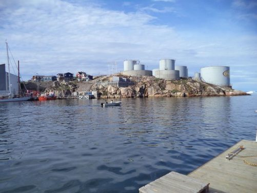 View across Ilulissat harbour. Storage tanks and houses on the far side. A small boat heading out.