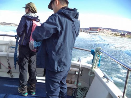 On-board a small boat leaving Ilulissat. Two fellow passengers standing in the foreground. Buildings of the town in the near distance. The large red and white building is Ilulissat's hospital.
