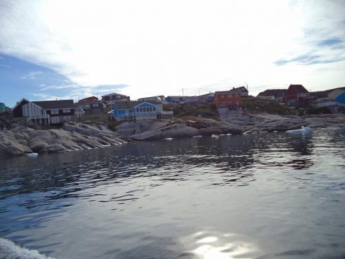 The boat close to the shore with houses extending down to almost the edge of the sea.