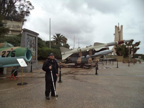 Tony with various weaponry in the background outside the Algeria Army Museum.
