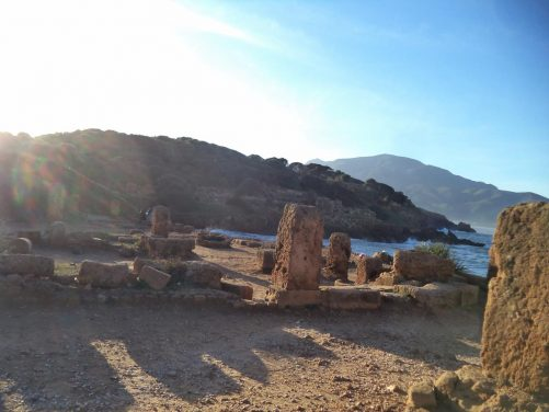View from near the ancient road showing ruins extending around a bay.