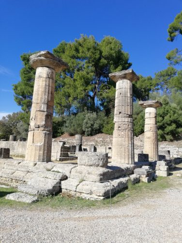 Closer view of the Temple of Hera. In view are three restored columns on a stone platform. The bases of other columns also survive.