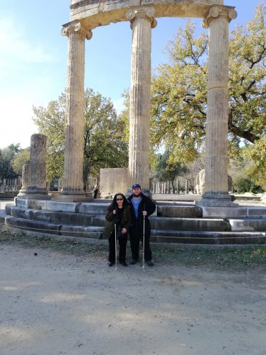 Tatiana and Tony in front of a colonnade made up of three reconstructed stone columns. This is part of the Philippeion, a circular monument which was commissioned by Philip II of Macedon in celebration of his victory at the battle of Chaeronea in 338 BC. The outer colonnade originally comprised of 18 columns.