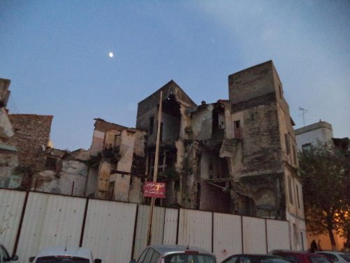 View of a partly demolished building. Low light with the moon above.