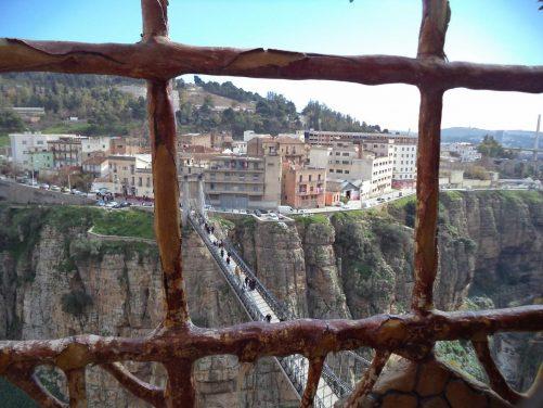 View through metal bars on a balcony towards the Mellah Slimane Bridge (also known as Perregaux footbridge) which spans the city's dramatic deep ravine.