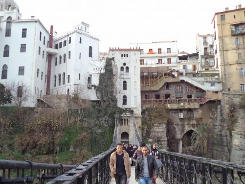 View of people crossing the Mellah Slimane Bridge with the elevator up to the old town at the end.