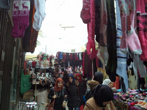 An outdoor market with stalls piled high with shoes and clothes.