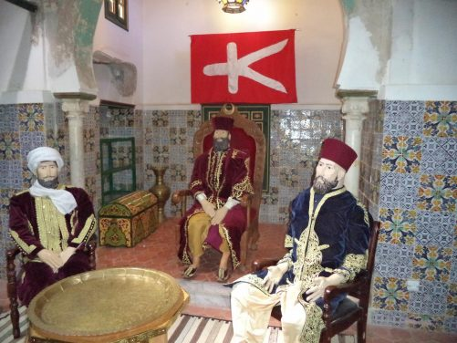 Inside Bey's Palace or Ahmed Bey Palace. A tiled room with three manikins in traditional dress sitting on chairs amongst old furniture.
