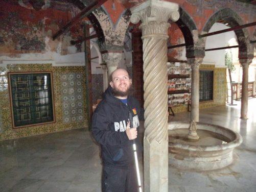 Tony by a thin column of twisted Italian marble in a courtyard. A circular fountain alongside.