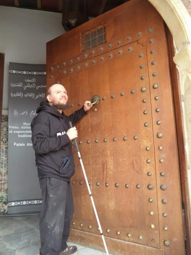 Tony holding a metal knocker on a large external door into the palace.