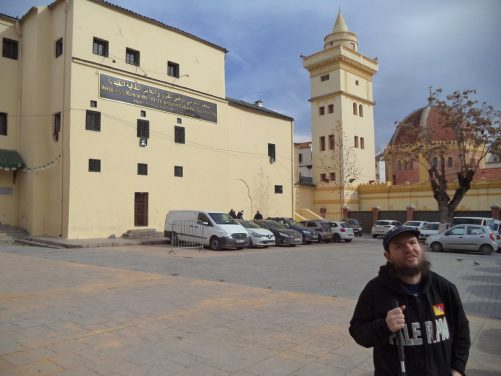 Tony outside the palace. The exterior is plain with pale yellow painted walls and small windows.