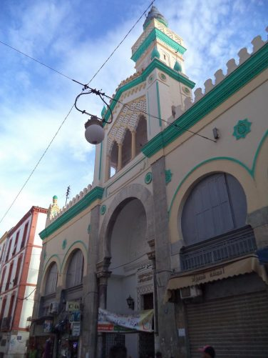 Outside an old building painted in green and cream, possibly a mosque.