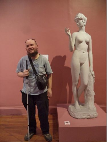 Tony next to a classical style sculpture depicting a female nude.