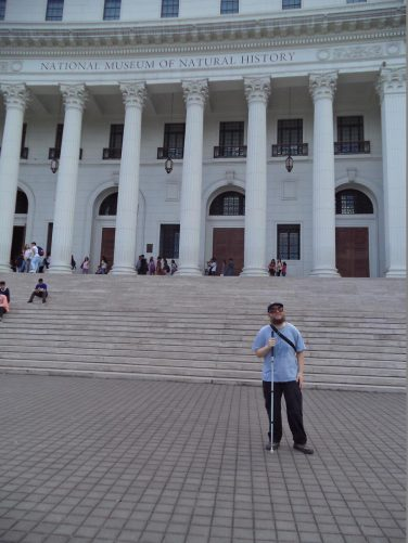 Tony in front of steps outside the National Museum. The façade is neoclassical in style.